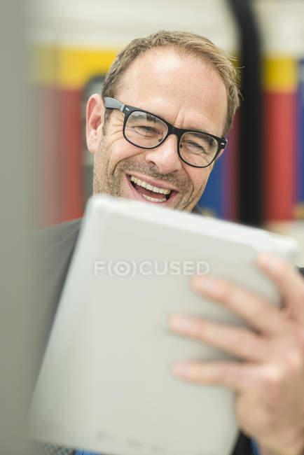 Uomo d'affari in occhiali da vista utilizzando tablet digitale — Foto stock