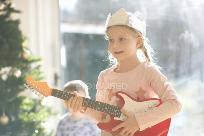Дівчина грає з іграшкової гітари на Різдво — стокове фото