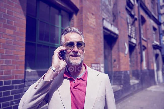 Mature man walking along street and talking by phone — Stock Photo