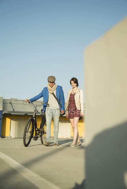 Young couple pushing bicycle along street — Stock Photo