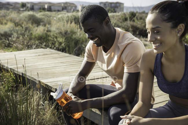 Casal vestindo roupas esportivas sentado na passarela de madeira — Fotografia de Stock