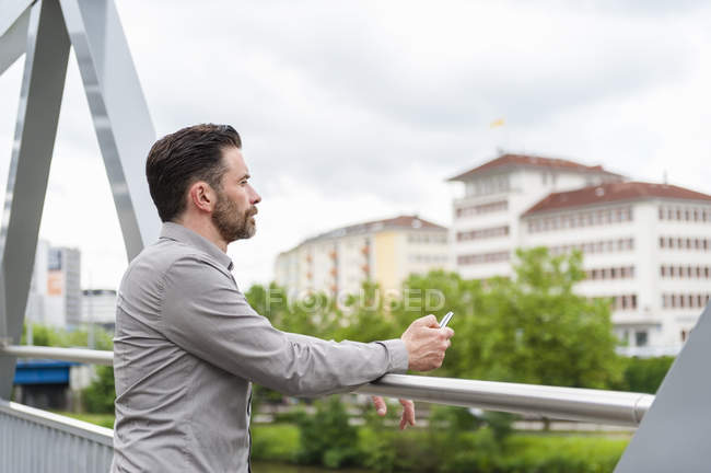 Mature businessman with smartphone  looking out from footbridge — Stock Photo