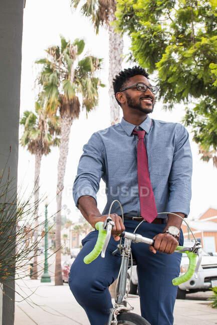 Молодой человек на велосипеде, улыбается — стоковое фото