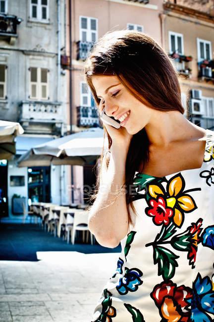 Молодая женщина чата на смартфоне на улице, Кальяри, Сардиния, Италия — стоковое фото