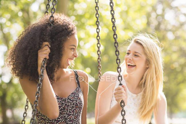 Две девушки сидят на качелях в парке и смеются — стоковое фото