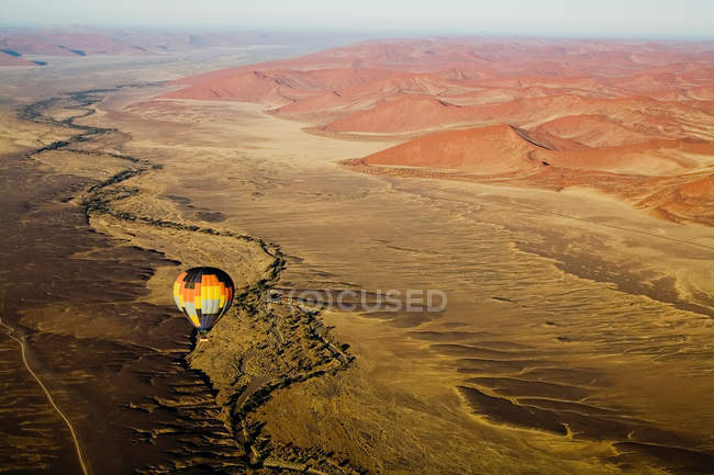 Hot air balloon floating over desert landscape — Stock Photo