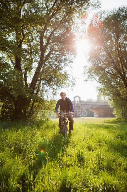 Велосипед їзда людина в галузі — стокове фото