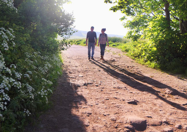 Rear view of couple walking on dirt track — Stock Photo