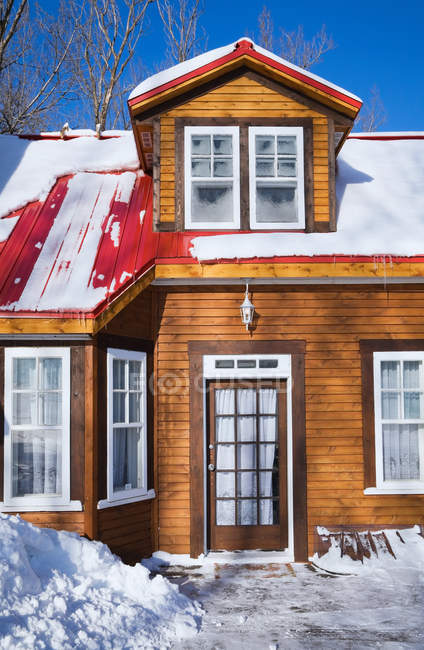 Wooden House exterior in snow against blue sky — Stock Photo