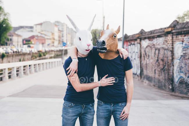 Retrato de dois homens com máscaras de coelho e cavalo na ponte urbana — Fotografia de Stock