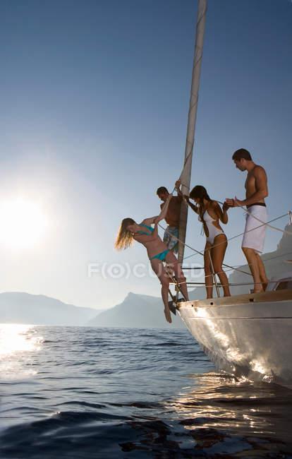 Hombres y mujeres en velero - foto de stock