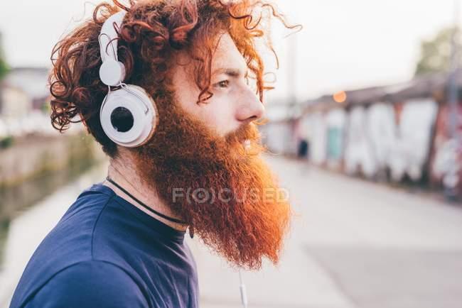 Jovem hipster masculino com cabelo vermelho e barba ouvindo fones de ouvido na cidade — Fotografia de Stock
