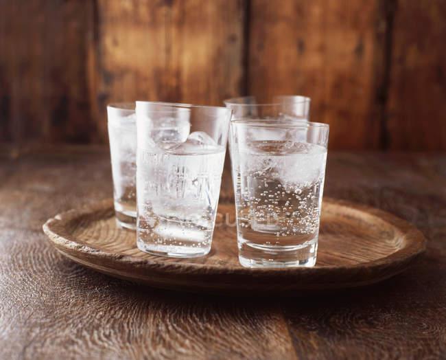 Sparkling water in drinking glasses with ice on vintage wooden plate — Stock Photo