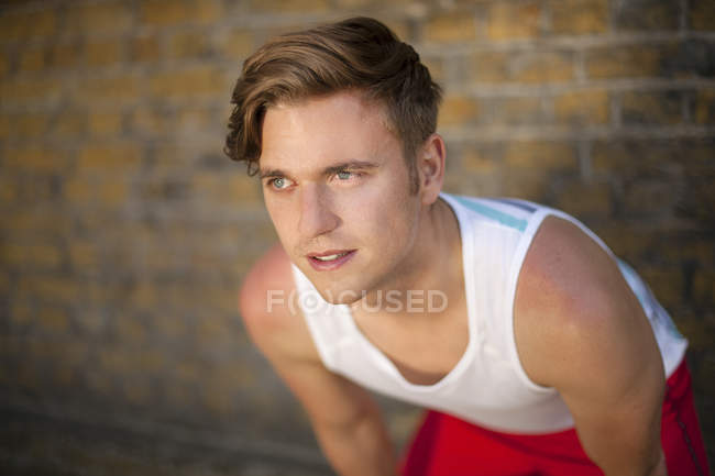 Runner stretching by brick wall — Stock Photo