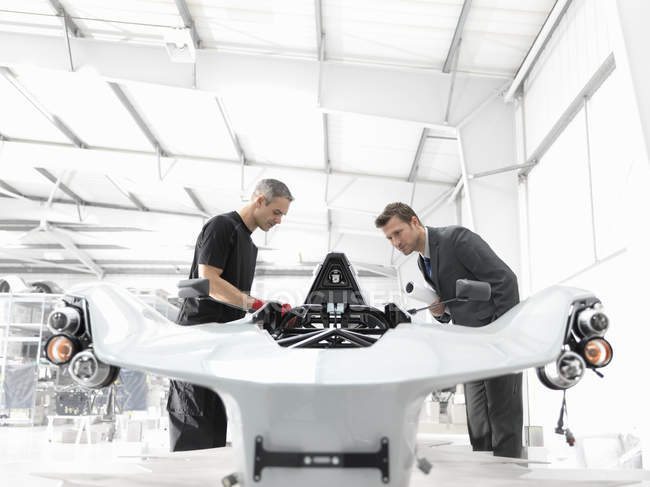 Engineer and automotive designer inspecting part-built supercar in car factory — Stock Photo