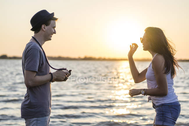 Young couple taking photograph by sea at sunset — Stock Photo