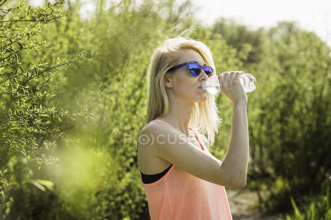 Молодая женщина в парке пьет бутылку воды — стоковое фото