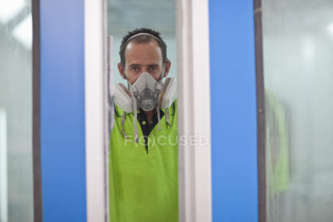 Portrait of carpenter in spray painting workshop doorway — Stock Photo