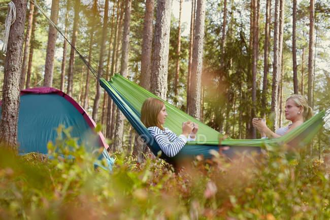 Mulheres relaxando em rede no parque de campismo — Fotografia de Stock