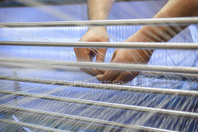 Close up of hands adjusting threads on industrial loom in textile mill — Stock Photo