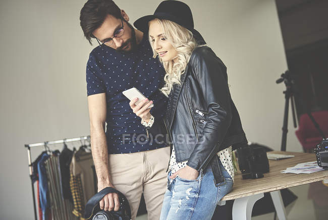 Photographer and stylist woman in hat looking at smartphone in photography studio — Stock Photo