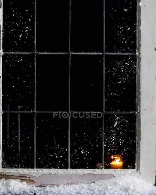 Candela che brucia in finestra di casa coperto di neve — Foto stock