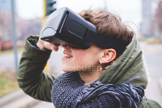Young woman outdoors, wearing virtual reality headset — Stock Photo