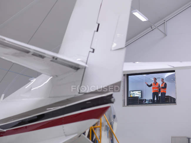 Engineers look out onto jet aircraft — Stock Photo