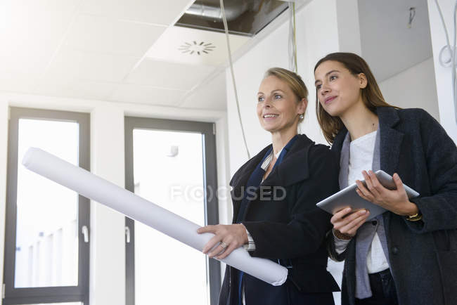 Businesswomen with blueprint inspecting in new office — Stock Photo