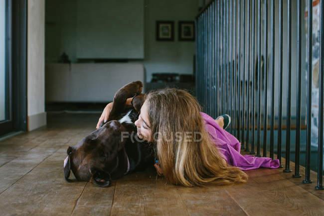 Girl lying on floor hugging dog — Stock Photo