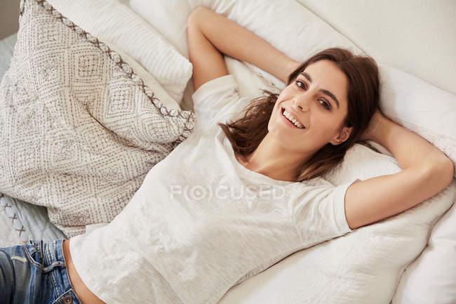 Alto angolo ritratto di bella giovane donna sdraiata sul letto — Foto stock