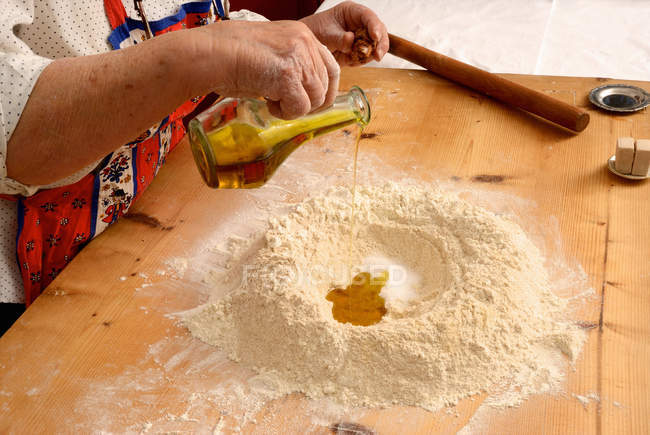 Cropped image of senior woman pouring olive oil in flour in kitchen — Stock Photo