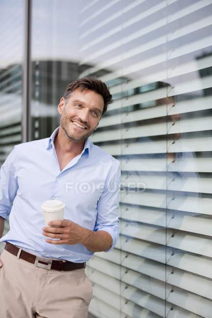 Porträt eines reifen Geschäftsmannes, der sich gegen Bürofenster lehnt und Kaffee trinkt — Stockfoto
