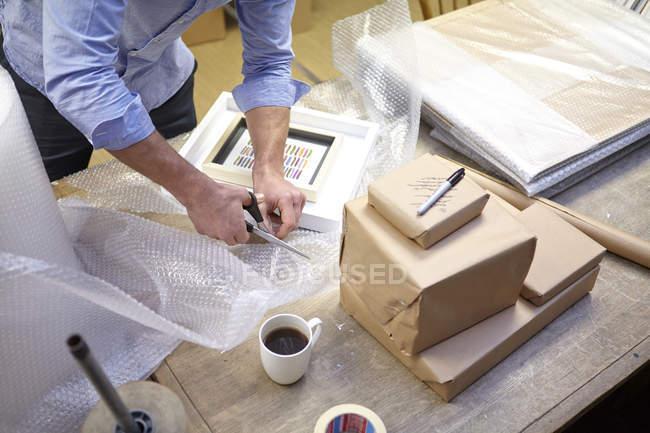 Человек режет пузырчатую пленку на столе в мастерской картин — стоковое фото