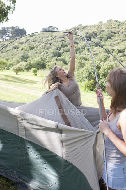 Two young females friends constructing tent — Stock Photo