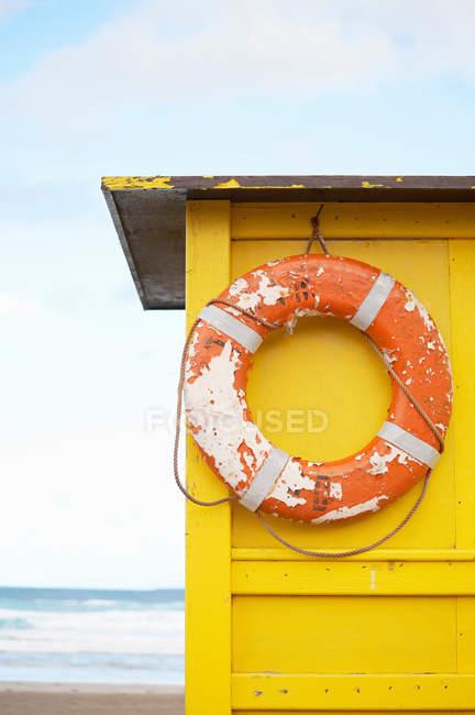 Gilet de sauvetage suspendu à la cabane sur la plage — Photo de stock