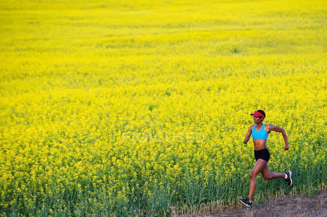 Jeune femme courant à côté du champ de colza — Photo de stock