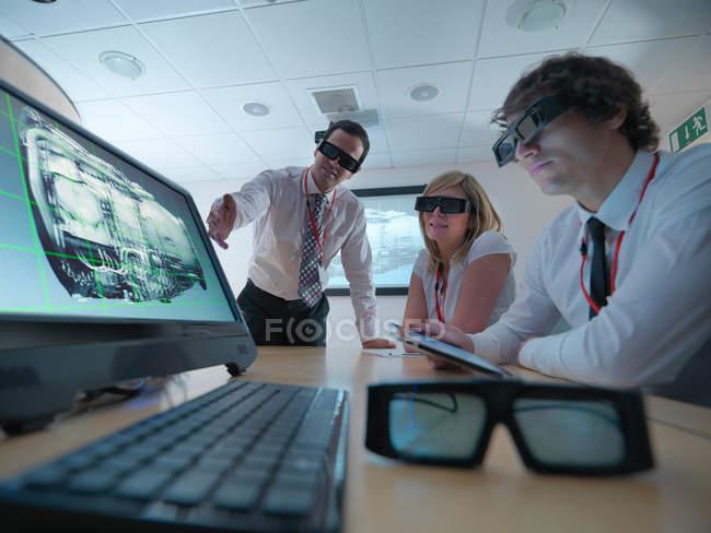 Engineers and apprentice in conference room wearing 3D glasses to look at 3D screens — Stock Photo