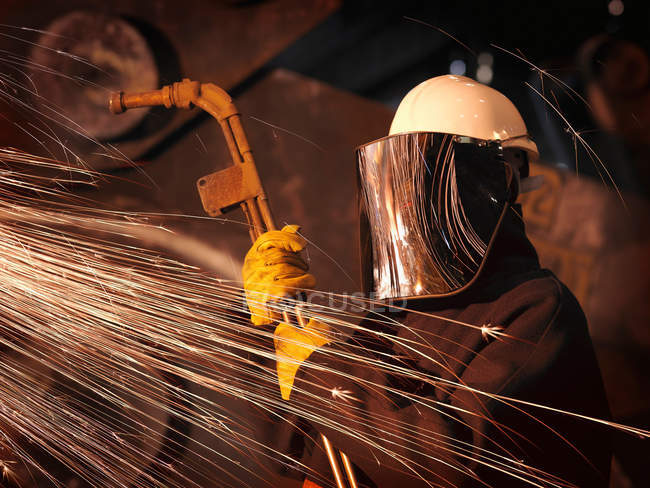Low angle view of worker with welding mask working in foundry — Stock Photo