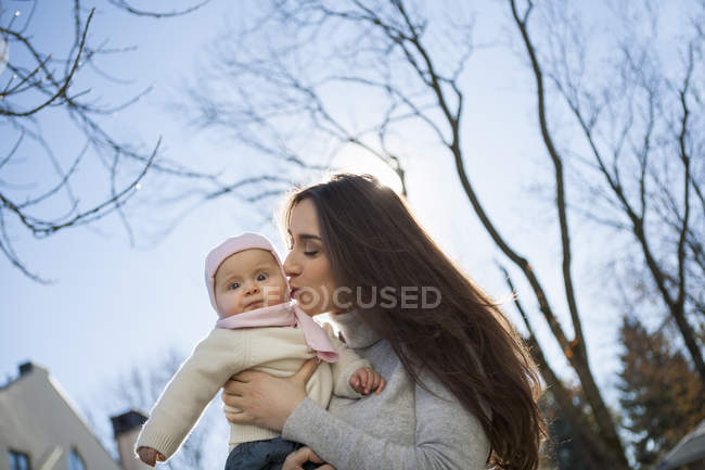 Mother kissing baby in arms — Stock Photo
