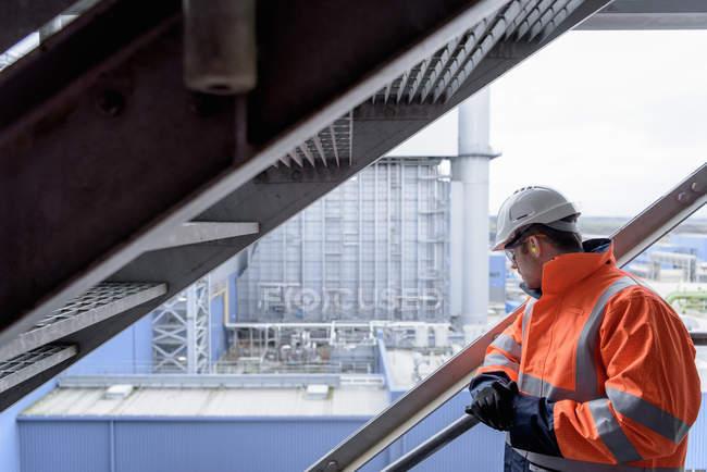 Trabajador mirando hacia fuera a la central eléctrica de gas - foto de stock