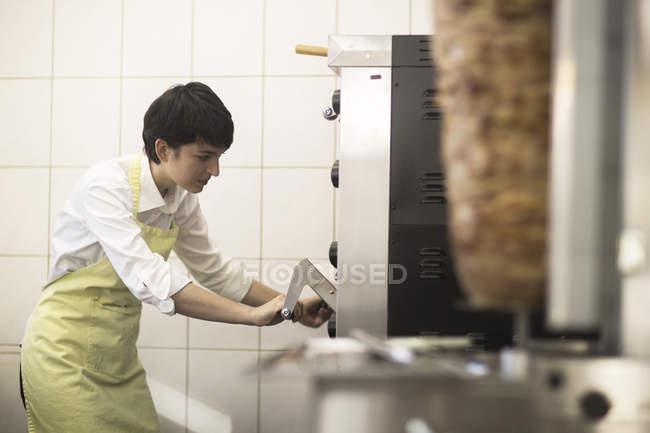Jeune femme, cuisson des aliments dans la boutique de restauration rapide — Photo de stock
