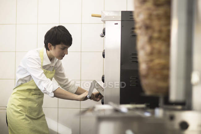 Young woman cooking food in fast food shop — Stock Photo