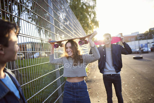 Young adult skateboarders greeting on sunlit street — Stock Photo