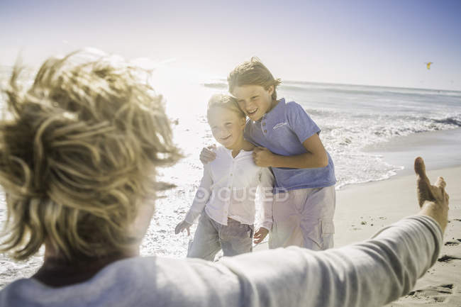 Father opening arms to sons on beach — Stock Photo