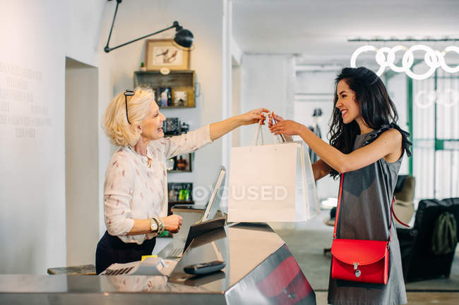 Assistante de vente distribuant des sacs à provisions clientèle — Photo de stock