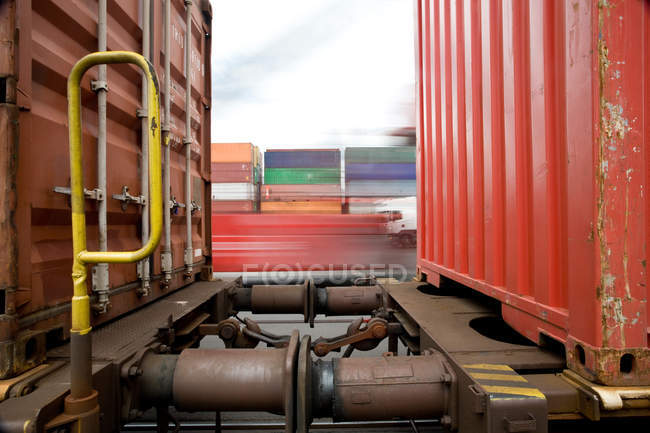 Train passing shipping containers — Stock Photo