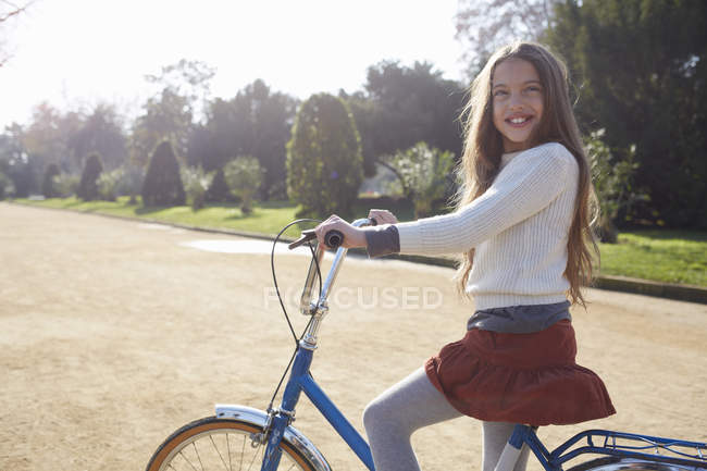 Girl sitting on bicycle in park looking at camera smiling — Stock Photo