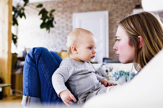 Середині дорослої жінки і дочка baby кривитися на дивані — стокове фото