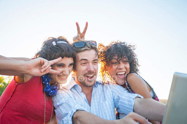 Young man and women making gestures at digital tablet — Stock Photo